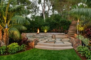 raised flagstone fire pit surrounded by tropical trees and low it walls