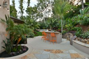barbecue and outdoor dining space surrounded by foliage